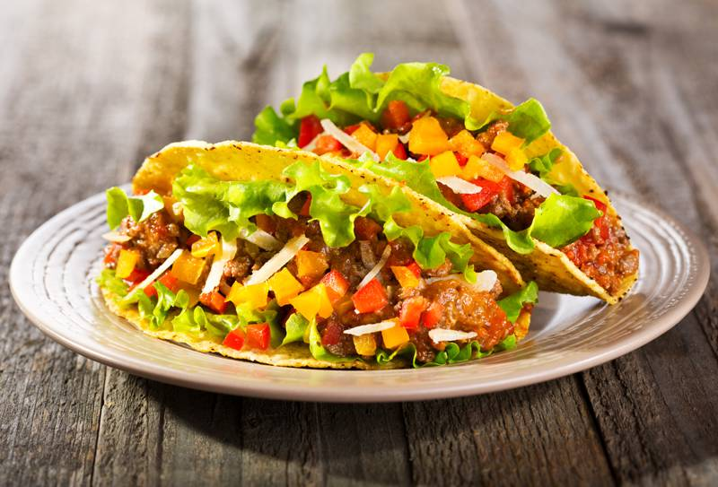 A close up shot of two well-filled tacos on a plate that is on a wooden table.