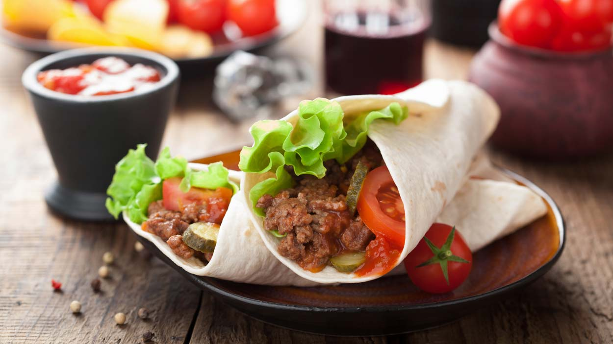Tortilla wraps or burritos on a plate that is on a wooden table with some condiments in the background