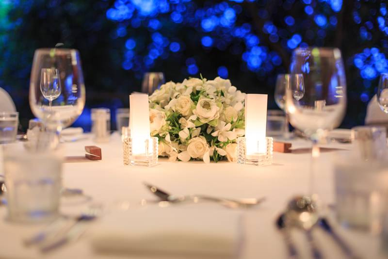 Close up picture of a wedding or quinceañera table with flowers in the middle, glasses, silverware, and napkins. Blurred background with blue LED lights.